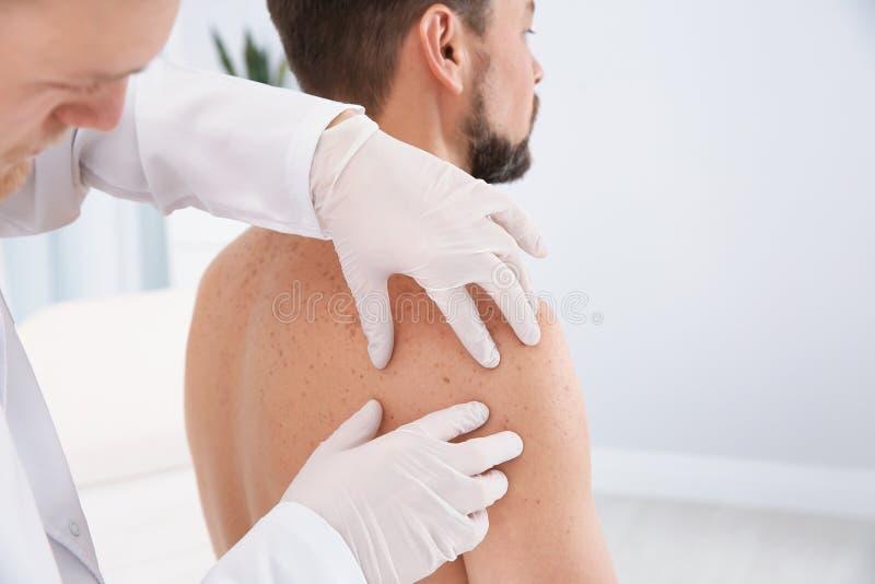 Dermatologist examining patient`s birthmark. In clinic royalty free stock photos