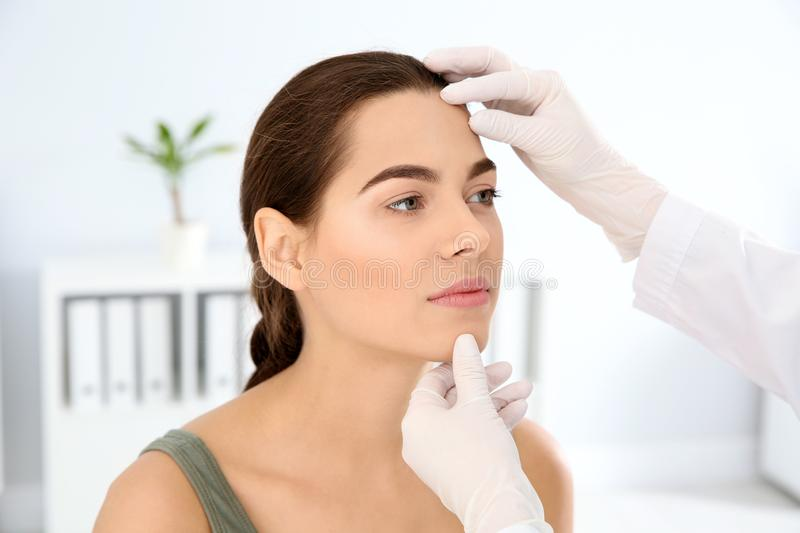 Dermatologist examining patient`s face in clinic. Skin cancer checkup royalty free stock photography