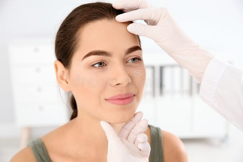 Dermatologist examining patient`s face in clinic. Skin cancer checkup royalty free stock photos