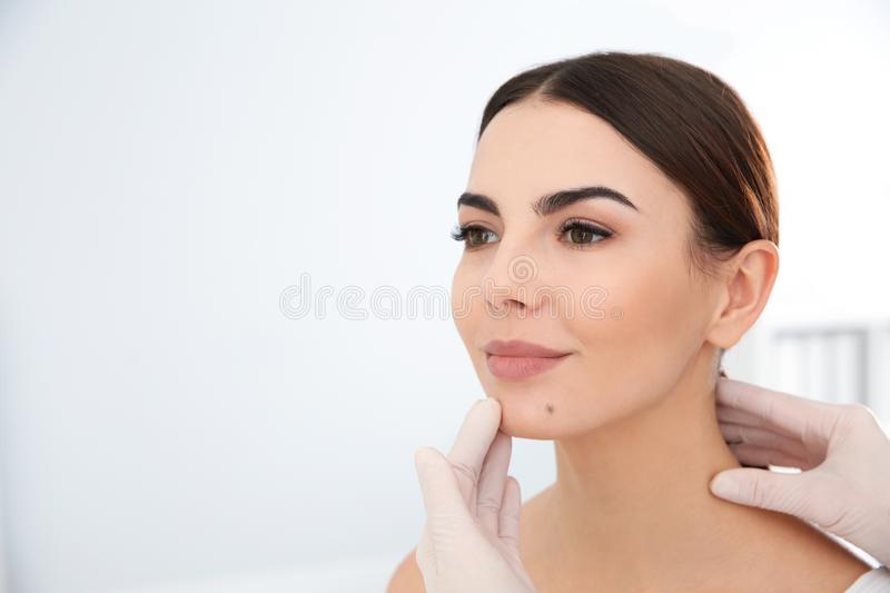 Dermatologist examining young patient`s birthmark in clinic. Space for text royalty free stock photography