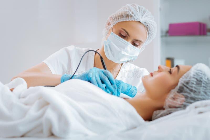 Dermatologista esperto profissional que usa um dispositivo moderno imagens de stock