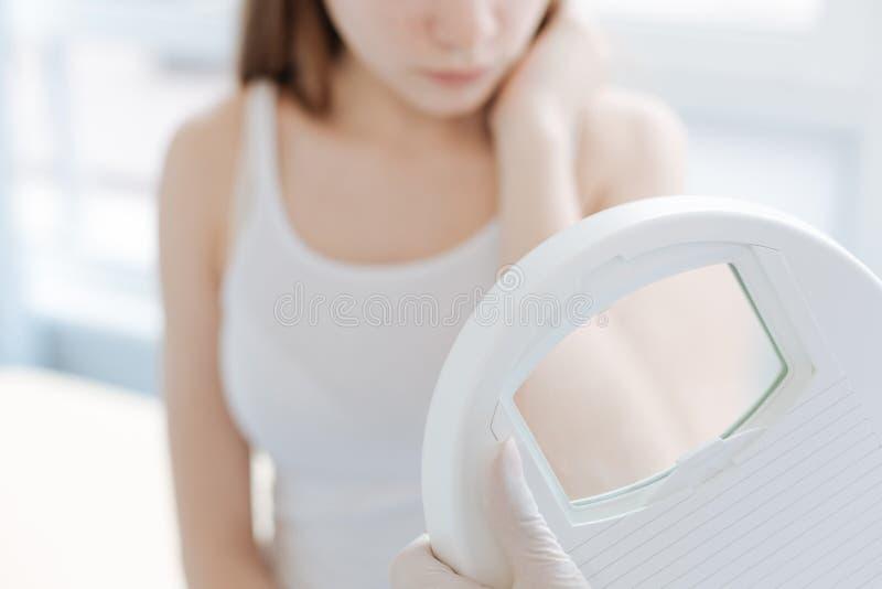 Dermatologista profissional que usa a lupa médica para o exame da pele no trabalho imagens de stock