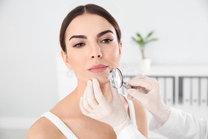 Dermatologista que examina a marca de nascença do paciente novo com lupa fotografia de stock royalty free