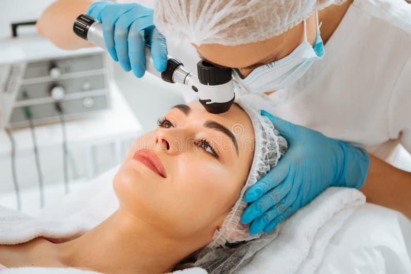 Dermatologue féminin qualifié à l'aide de l'équipement professionnel moderne image stock