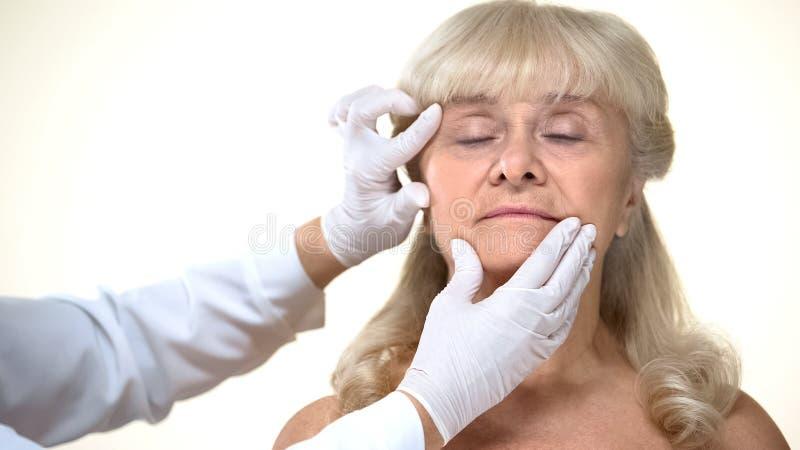 Dermatoloog die bejaarde vrouwelijke geduldige huid, rimpelsverwijdering, schoonheid onderzoeken royalty-vrije stock fotografie