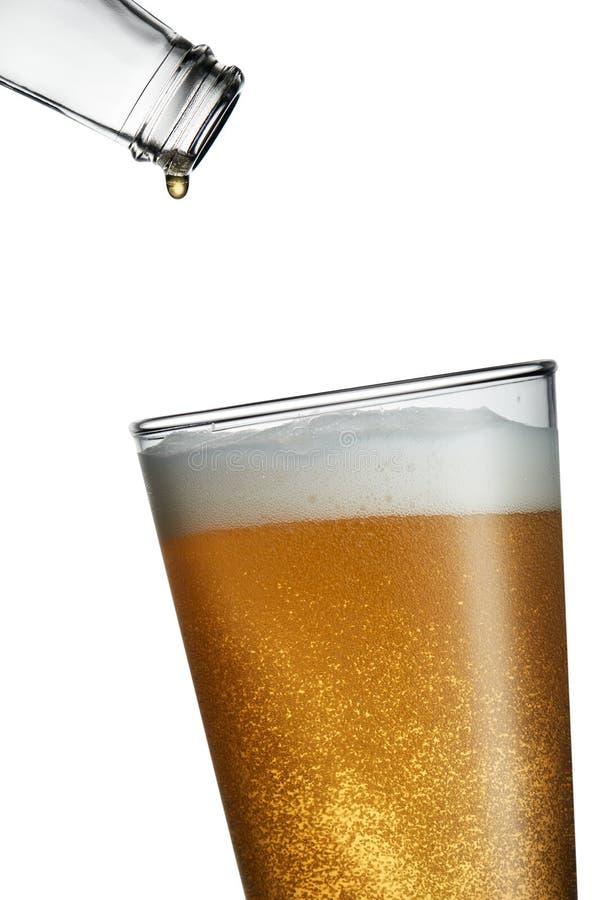 Dernière baisse de bière d'une bouteille vide tombant dans un plein verre photo libre de droits