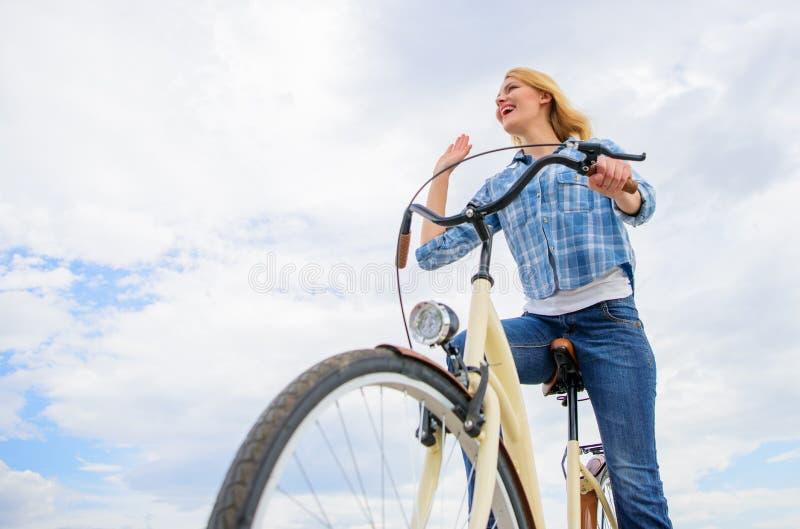 Dernières nouvelles pour les cyclistes récréationnels et de loisirs La fille monte le fond de ciel de vélo La femme émotive ont p photographie stock