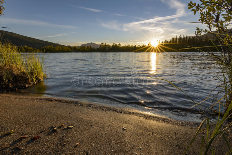 Derniers rayons de soleil pendant le coucher du soleil tranquille au-dessus du lac calme, Suède photo stock