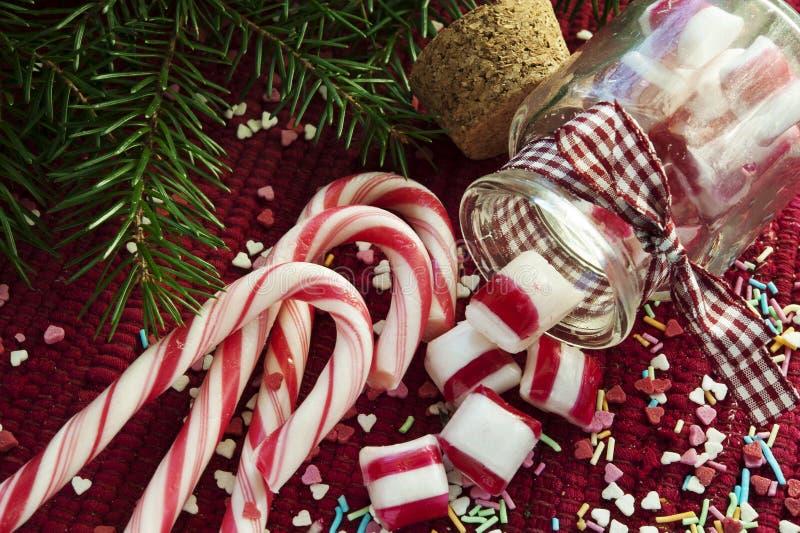 Derramado/vertió de los caramelos dulces del tarro de cristal en el CCB rojo de la Navidad fotografía de archivo
