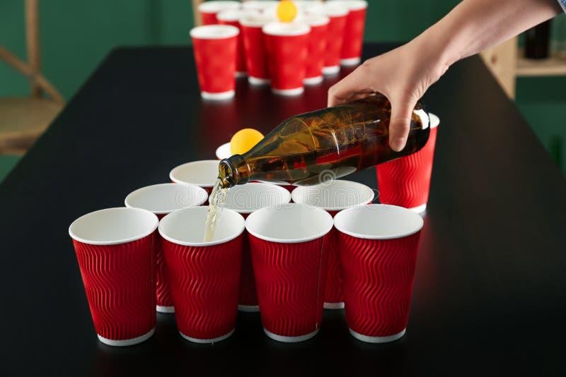 Derramamento da cerveja da garrafa de vidro em copos plásticos na tabela Jogo do pong da cerveja fotografia de stock royalty free