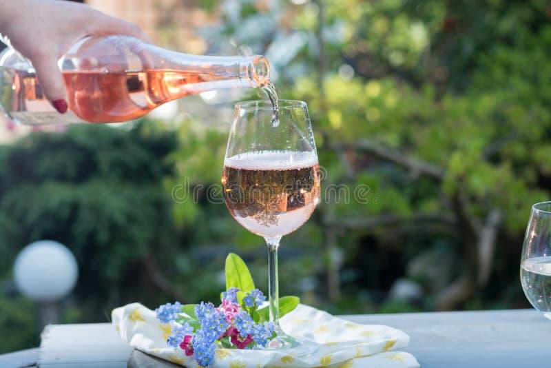 Derramamento do garçom glas do vinho cor-de-rosa frio, terrase exterior, ensolarado fotografia de stock