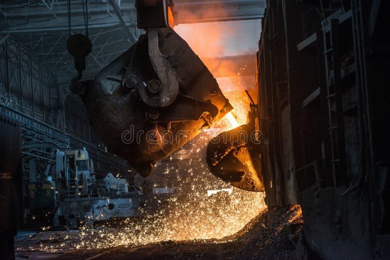 Derramamento do metal líquido na fornalha da aberto-lareira fotografia de stock