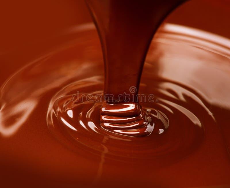 Derramamento líquido do chocolate quente foto de stock