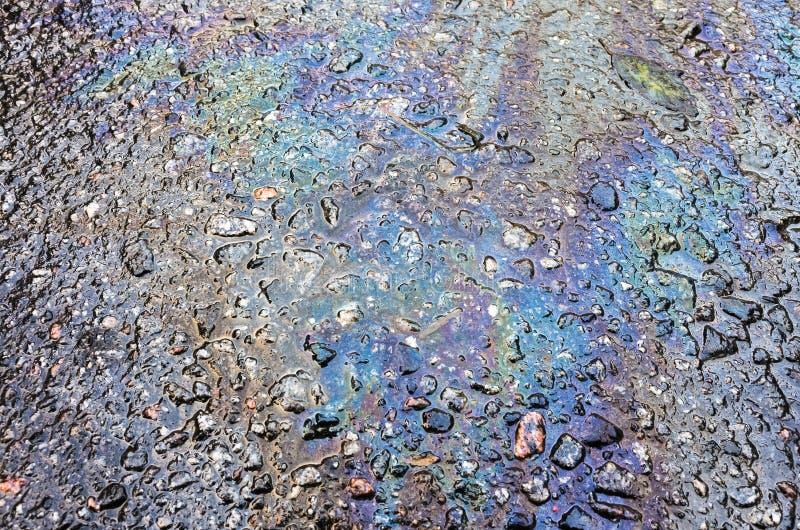 Derramamiento de la gasolina en la carretera de asfalto imagenes de archivo