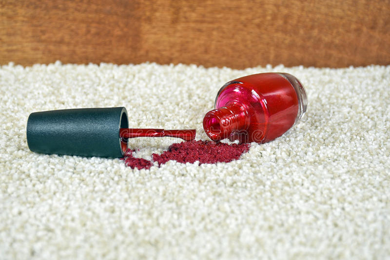 Derramamiento rojo del esmalte de uñas en la alfombra foto de archivo