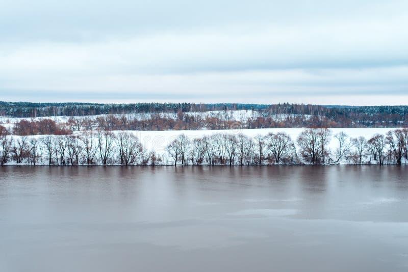 Derramando o rio no inverno contra o contexto dos montes brancos de uma floresta coberto de neve bonita na distância limpo fotografia de stock