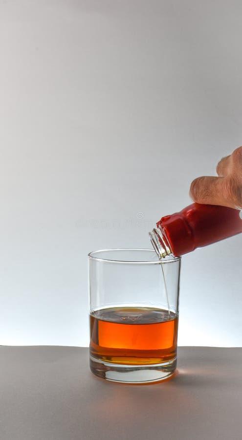 Derramando um vidro do uísque de bourbon no contexto branco fotografia de stock royalty free