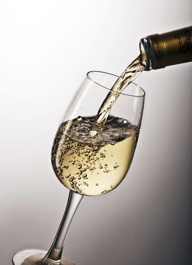 Derramando um vidro do vinho branco imagem de stock