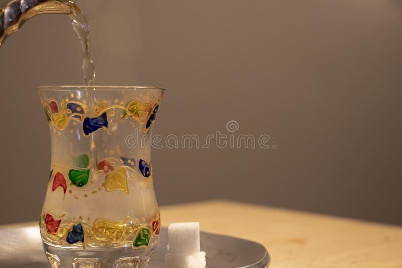 Derramando um vidro quente do chá da hortelã imagens de stock royalty free