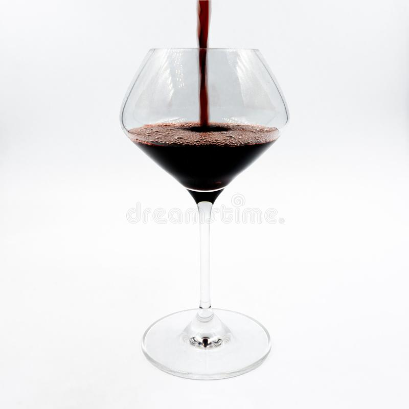 Derramando um vinho tinto em um copo de vinho imagens de stock