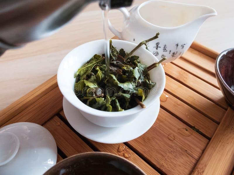 Derramando uma água fervida à embarcação da fabricação de cerveja do chá com as folhas do chá do oolong no chá que drena a bandej foto de stock royalty free
