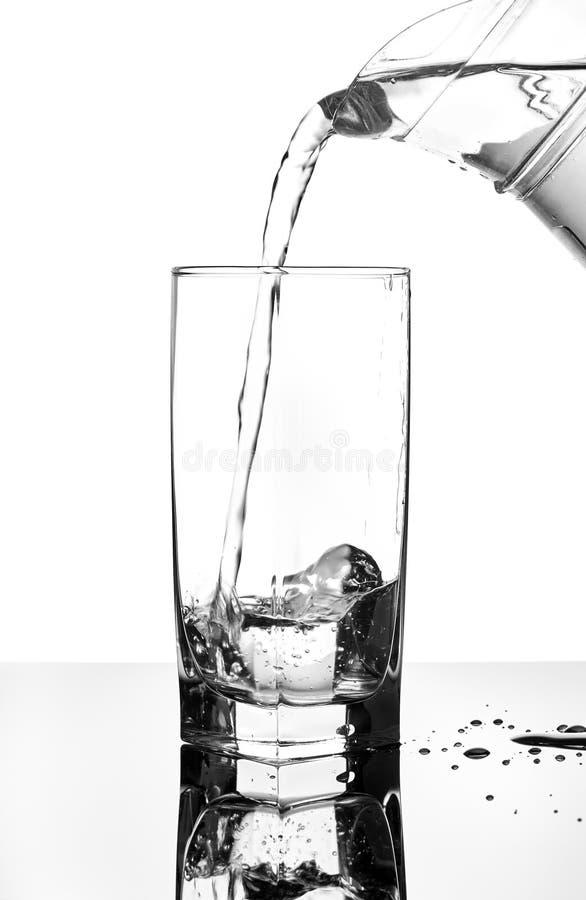 Derrame a água de um jarro em um vidro fotos de stock