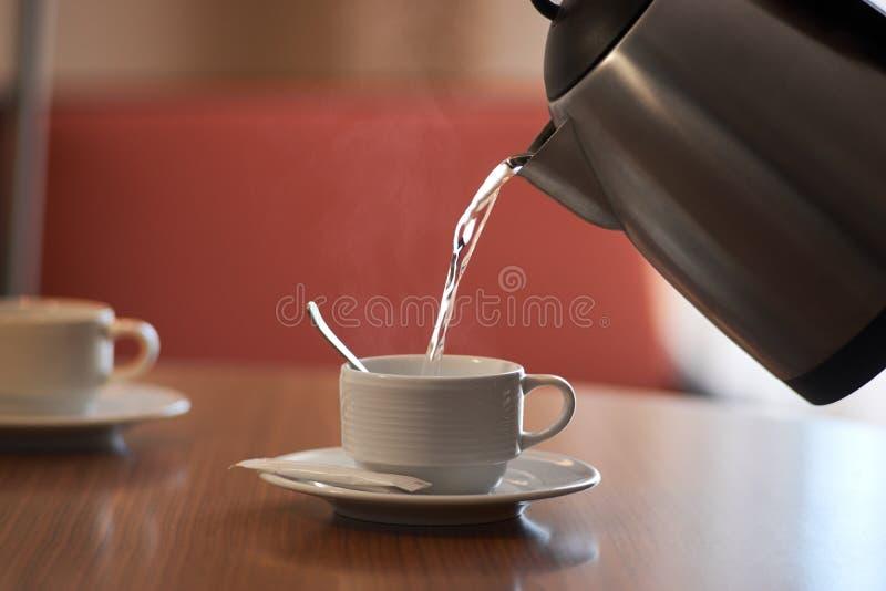 Derrame a água a ferver da chaleira no copo foto de stock royalty free
