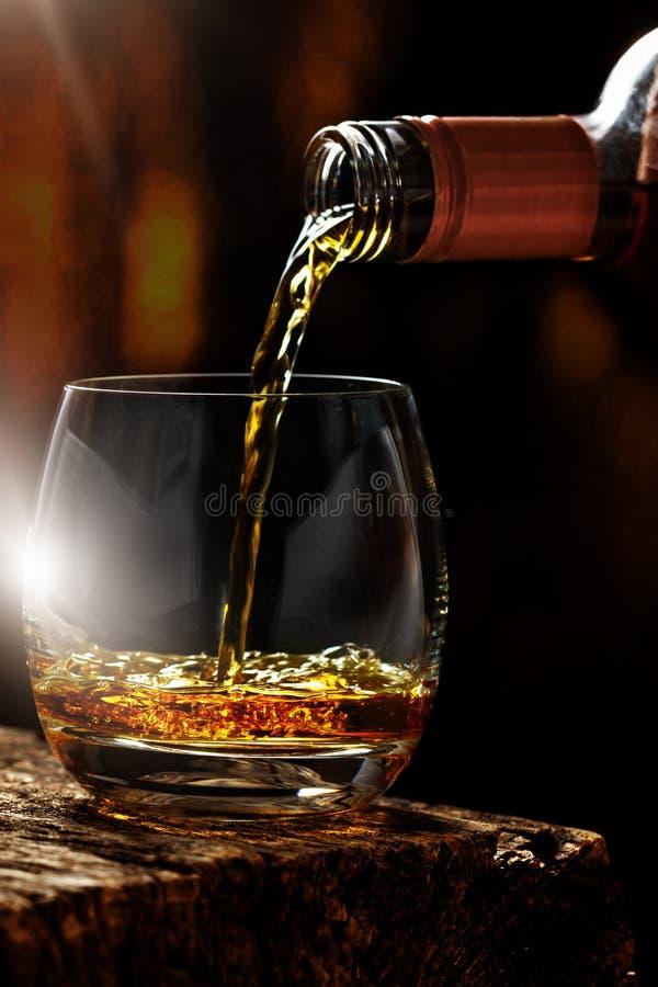 Derrame o uísque fora da garrafa em um vidro fotografia de stock