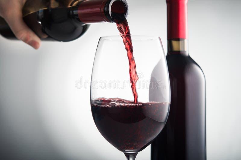 Derrame o vinho tinto no vidro fotografia de stock royalty free
