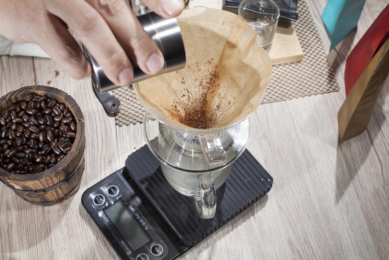 Derrame os feijões de café triturados em um cervejeiro que do café se usar derrama sobre o método V60 fotografia de stock royalty free