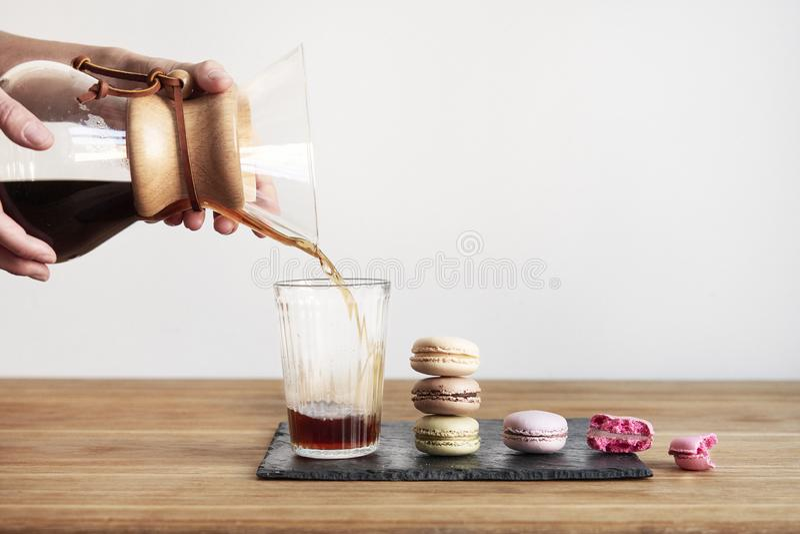 Derrame sobre o método Chemex da fabricação de cerveja do café, posse das mãos da mulher uma bacia de vidro, ainda vida com as co fotografia de stock