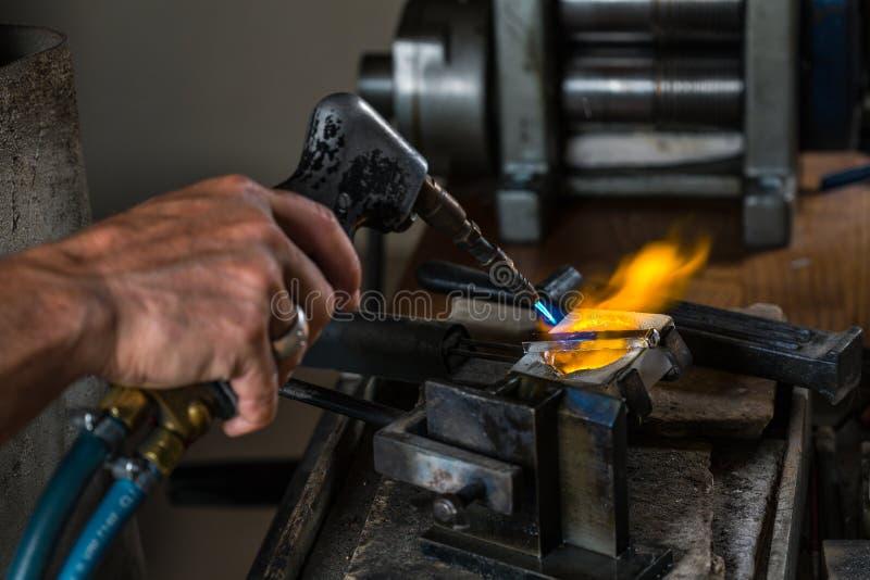 Derretendo um lingote de prata no cadinho com maçarico; foto de stock