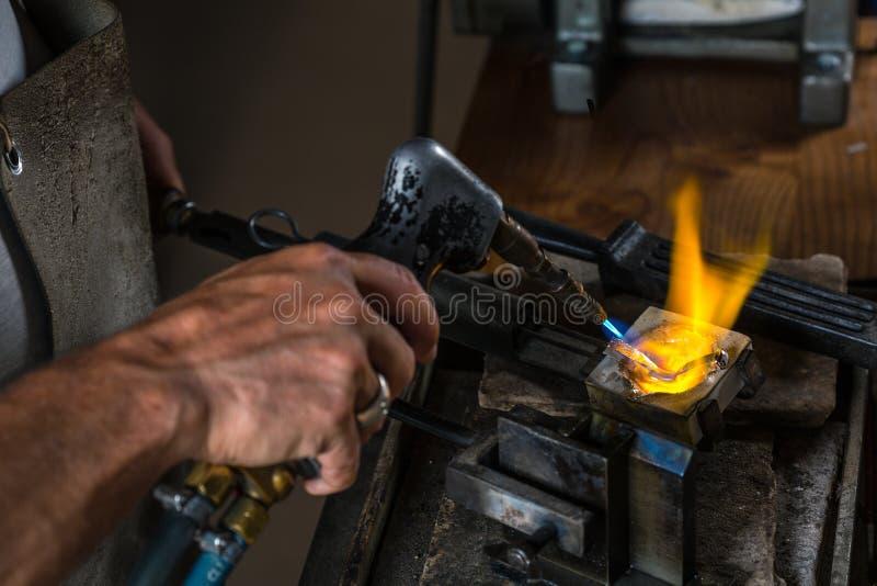 Derretendo um lingote de prata no cadinho com maçarico; fotos de stock