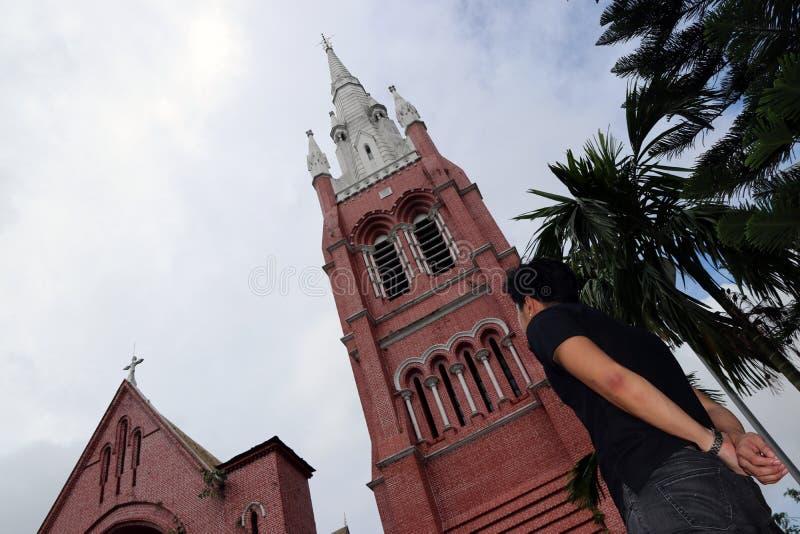 Derrière de l'homme se tenant devant le bâtiment principal de l'église et de la tour d'église à la cathédrale de la trinité saint photos stock