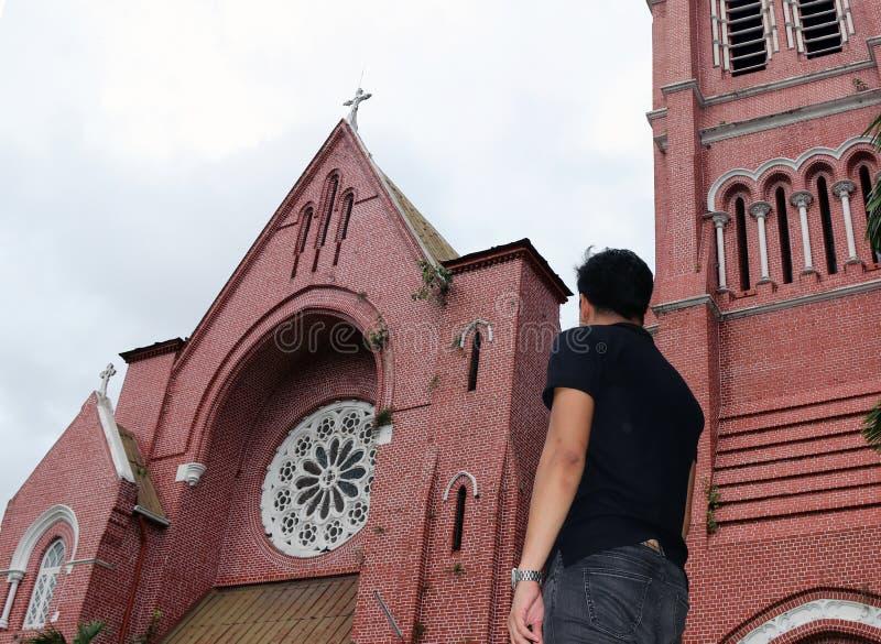 Derrière de l'homme se tenant devant le bâtiment principal de l'église et de la tour d'église à la cathédrale de la trinité saint photo libre de droits