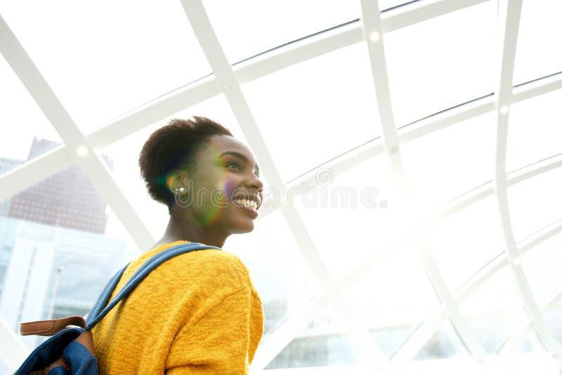 Derrière de la jeune femme heureuse à la station avec le sac à dos photo stock
