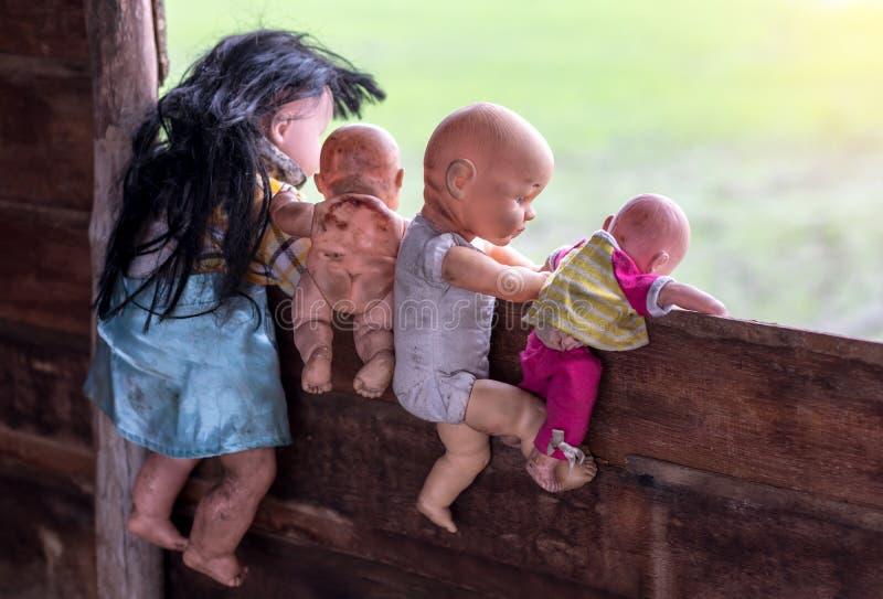 Derrière de vieilles poupées de bébé s'élevant sur le mur en bois photo stock