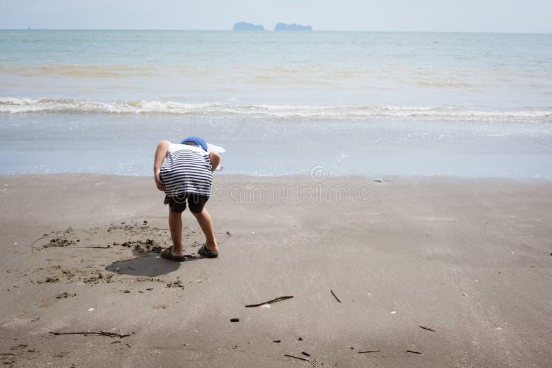 Derrière du garçon recherchant le concept de bernard l'ermite et d'éboueur photo libre de droits