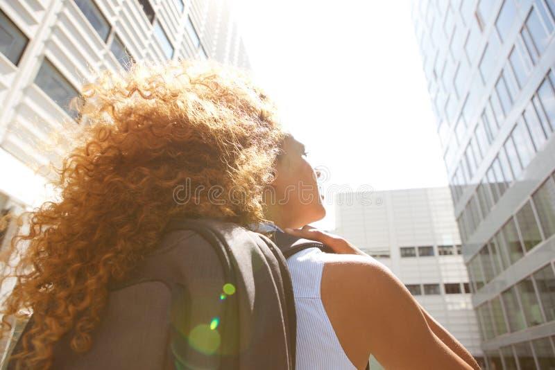 Derrière la jeune femme marchant et regardant des bâtiments images libres de droits
