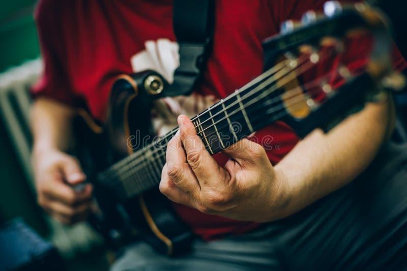 Derrière la scène Pratique en matière de guitariste jouant la guitare dans la musique malpropre s image stock