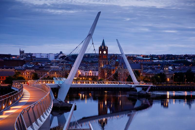 Derry, Ireland. Illuminated Peace bridge in Derry Londonderry, City of Culture, in Northern Ireland with city center at. The background. Night cloudy sky with royalty free stock photo