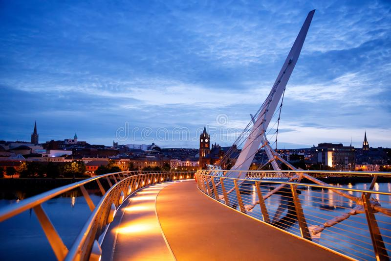 Derry, Ireland. Illuminated Peace bridge in Derry Londonderry, City of Culture, in Northern Ireland with city center at. The background. Night cloudy sky with royalty free stock images