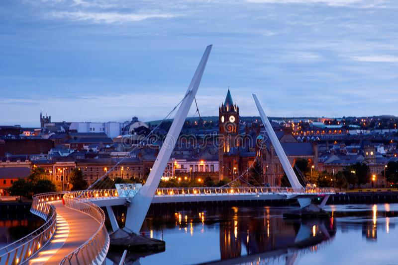 Derry, Ireland. Illuminated Peace bridge in Derry Londonderry, City of Culture, in Northern Ireland with city center at. The background. Night cloudy sky with stock photography