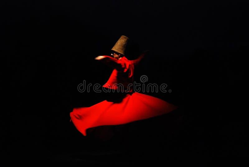 Derviscio girantesi su fondo nero in costume rosso immagini stock libere da diritti