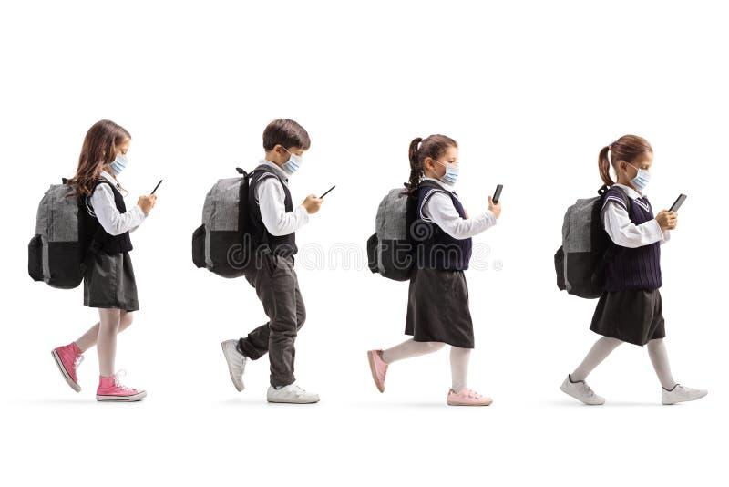 Des écoliers munis de masques protecteurs pour le visage marchant dans la queue et tenant des téléphones portables photographie stock