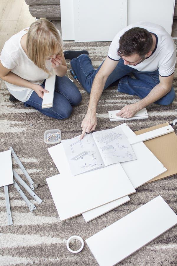 Des éléments blancs de meubles pour en kit sont présentés autour de la salle La femme et l'homme s'asseyent sur le tapis et sont  image libre de droits