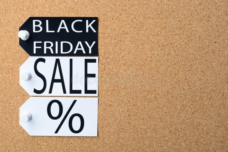 Des étiquettes de vente de Black Friday sont goupillées au panneau de liège photo libre de droits