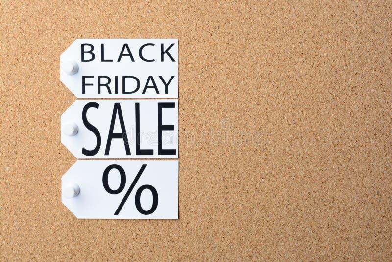 Des étiquettes de vente de Black Friday sont goupillées au panneau de liège photos libres de droits