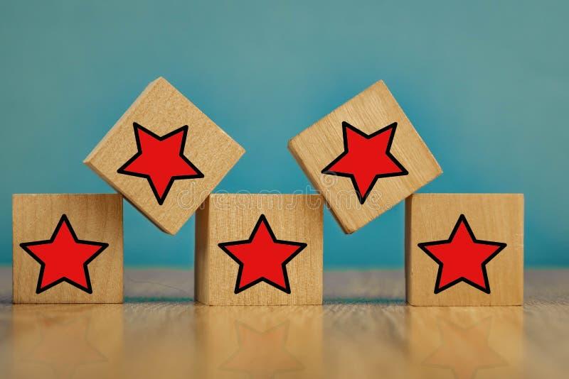 Des étoiles rouges sur des cubes en bois sur fond bleu Les étoiles signifient évaluer la qualité système de notation à cinq point images stock