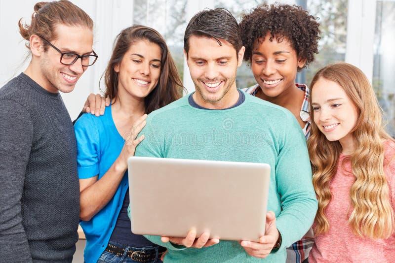 Des étudiants avec l'ordinateur portable sont excités au sujet de l'innovation image stock